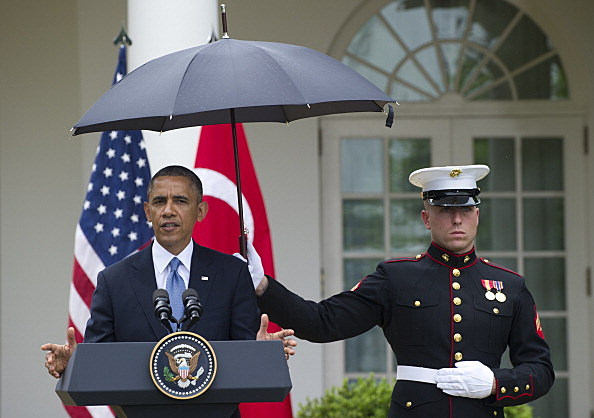 marine holding umbrella for president obama